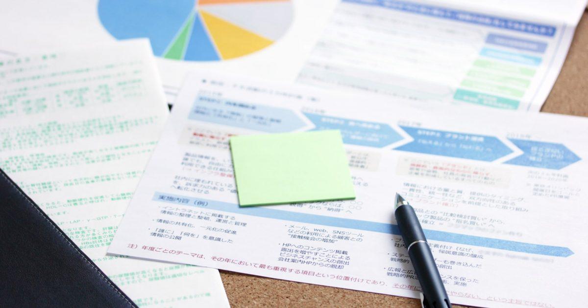資金の計画書の上にあるメモとペン