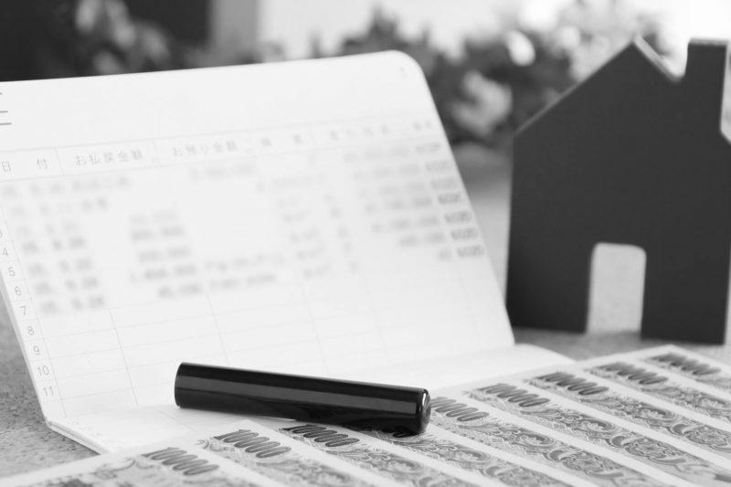 白黒の通帳と家模型