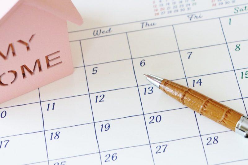 カレンダーの上にある家の模型とペン
