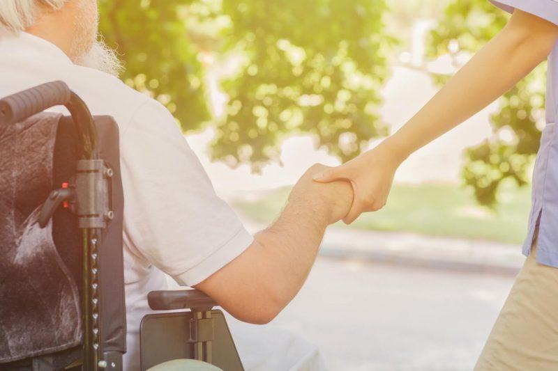 車椅子のお年寄りと手を差し伸べる人